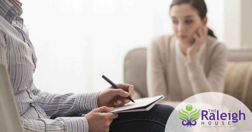 Young woman speaking to addiction professional during rehab intake.