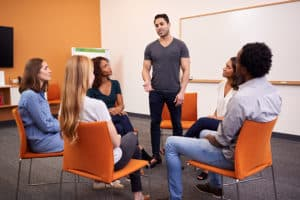 A man standing up and addressing a group of people in a therapy session.