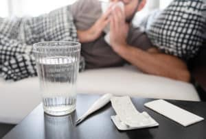 A man suffering from the flu because his immune system is compromised by heroin abuse.