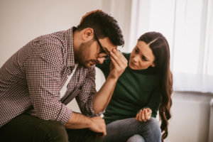 A man struggling with depression and being consoled by his wife.